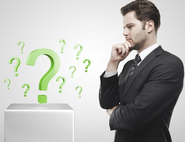 Hombre-con-traje-mirando-a-unas-interrogaciones-en-verde