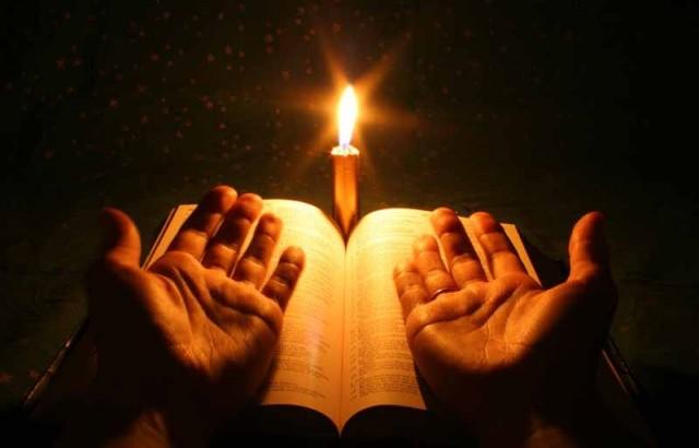 manos-rezando-con-vela-sobre-biblia